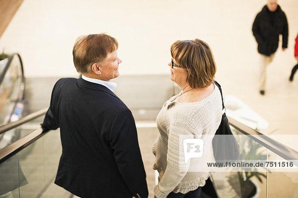 Rückansicht des Seniorenpaares auf einer Rolltreppe im Einkaufszentrum