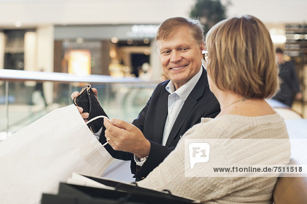 Happy senior man showing his shopping to woman in mall