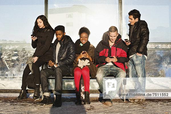Porträt einer jungen Frau mit mehreren ethnischen Freunden  die Mobiltelefone auf der Bank benutzen.