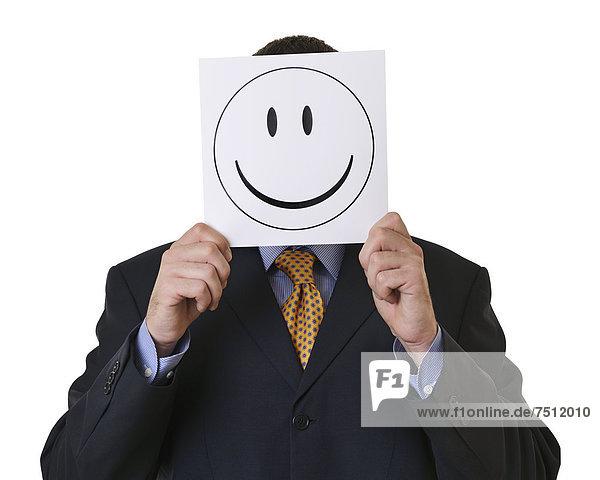 Ein Geschäftsmann hält einen Smiley vor sein Gesicht