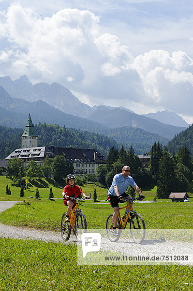 Cycling tour with mountain bikes  father and son in front of Schloss Elmau Castle  Mittenwald  Wetterstein Range  Werdenfelser Land  Upper Bavaria  Bavaria  Germany  Europe