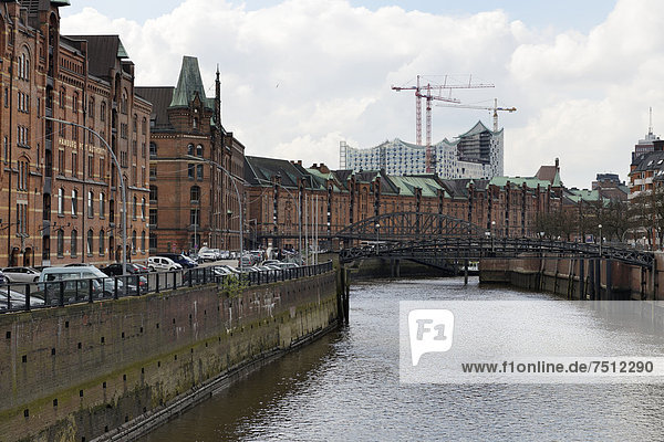 Warehouse buildings at Zollkanal canal  Jungfernbruecke bridge  Virgin and the Elbe Philharmonic Hall under construction at back
