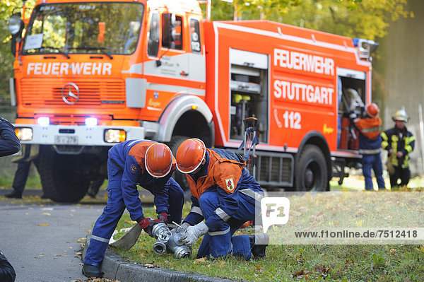 Final fire service drill of the young Stuttgart firefighters in autumn  teenagers setting up a hose  Stuttgart  Baden-Wuerttemberg  Germany  Europe