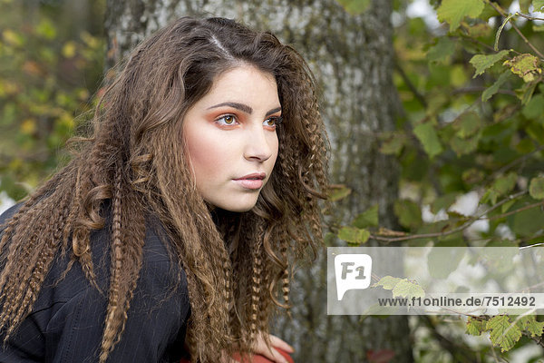 Young woman with long hair in front of a tree  portrait