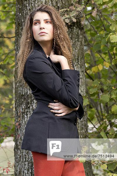 Junge Frau mit langen Haaren und schwarzem Blazer vor einem Baum
