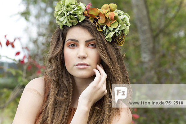 Young woman with a flowal wreath in her hair  outdoors  portrait