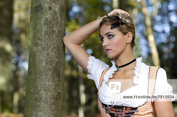 Junge Frau im Dirnd posiert an Baum  Portrait  Dirndllook