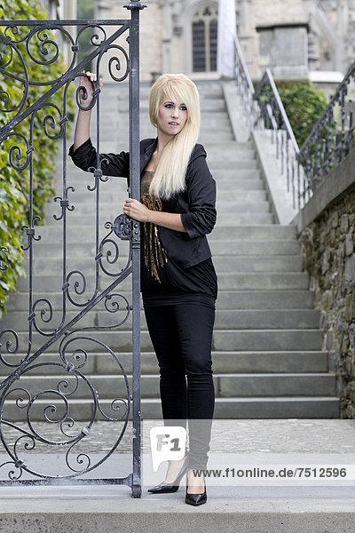 Junge Frau mit langen blonden Haaren  schwarzer Jacke und Hose posiert an Eingangstor