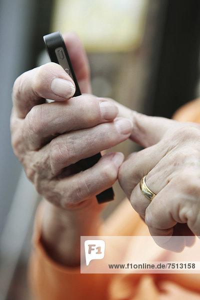 Seniorin mit Smartphone in der Hand