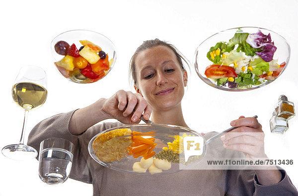 Junge Frau sitzt an einem Glastisch und isst Schnitzel mit Gemüse und Kartoffeln  Beilagensalat und Fruchtsalat als Nachspeise