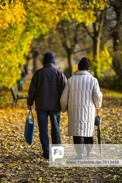 Senioren  Rentner  Paar bei einem Herbstspaziergang  Händchen haltend