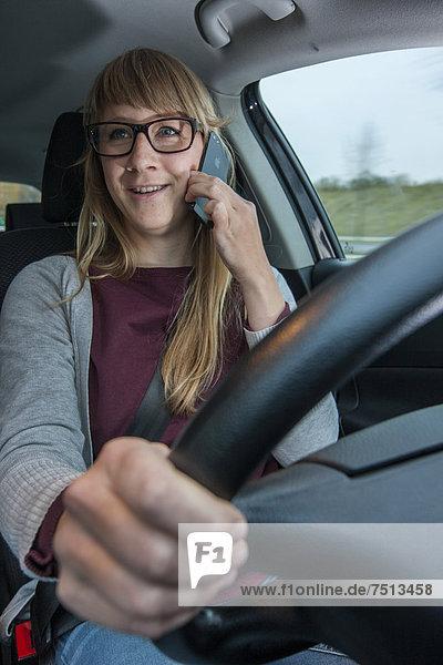 Junge Frau fährt Auto  telefoniert mit dem Handy während der Fahrt