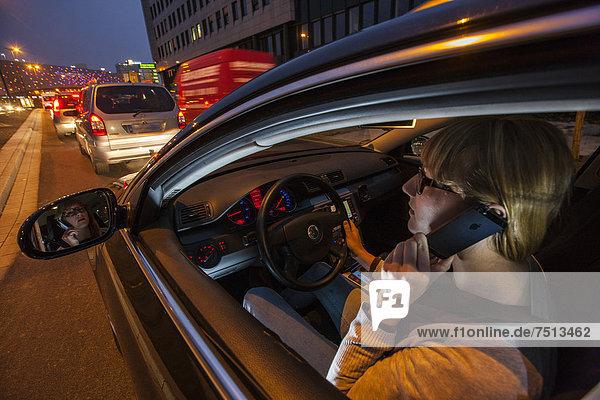 Junge Frau fährt Auto in der Innenstadt  abends  telefoniert mit dem Handy während der Fahrt