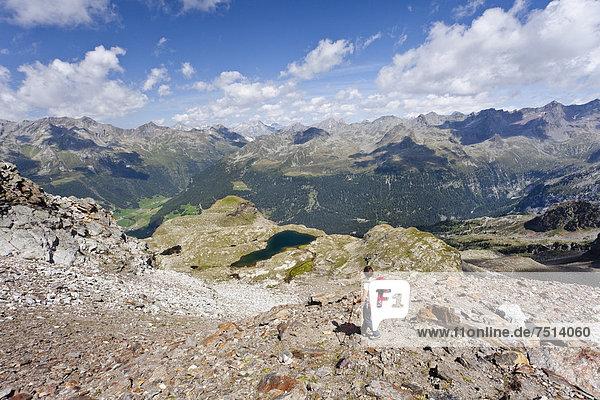 Bergsteiger beim Abstieg vom Schneebiger Nock in der Rieserfernergruppe im Pustertal  unten der große Malersee  Südtirol  Italien  Europa