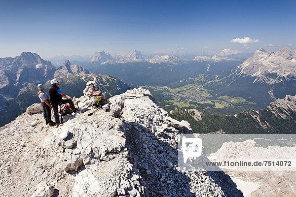 Bergsteiger auf dem Gipfel des Cristallo di Mezzo beim Aufstieg über die Via ferrata Marino Bianchi  Klettersteig am Monte Cristallo oberhalb von Cortina  hinten die Tofane  die Marmolata und der Pelmo  unten das Dorf Cortina  Belluno  Dolomiten  Italien  Europa