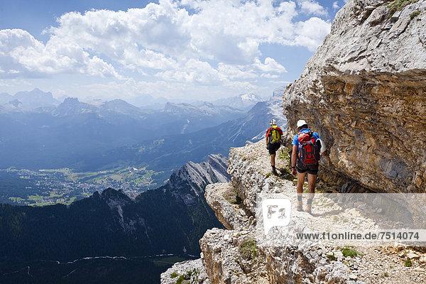 Bergsteiger beim Abstieg über die Via ferrata Ivano Dibona  Klettersteig am Monte Cristallo vom Gipfel des Cristallino  unten das Dorf Cortina  hinten die Marmolata  Belluno  Dolomiten  Italien  Europa