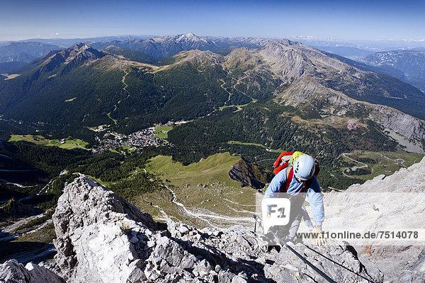 Bergsteiger beim Aufstieg über die Via ferrata Bolver-Lugli auf die Cima Vezzana in der Palagruppe  unten das Dorf San Martino di Castrozza  Trentino  Italien  Europa