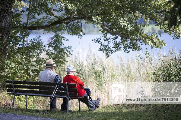 Elderly couple sitting on a bench beside the lake  Weissensee lake  Carinthia  Austria  Europe