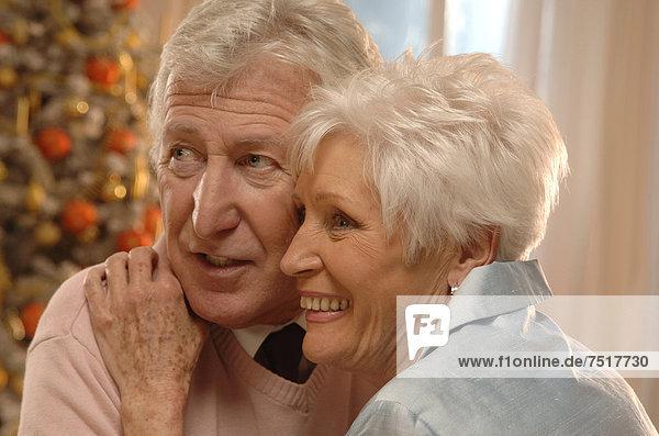 Älteres Pärchen verliebt vor dem Weihnachtsbaum