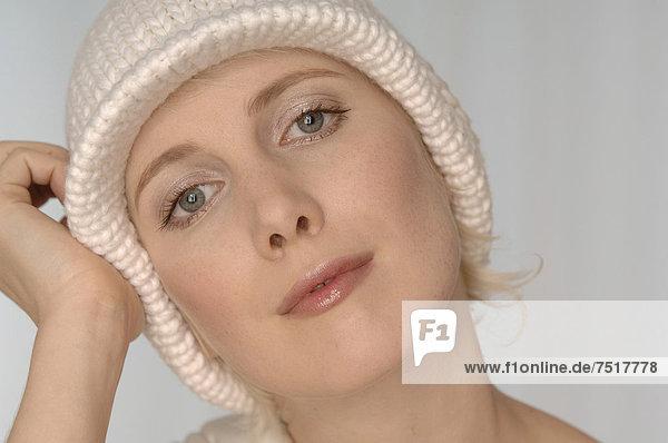 Blonde Frau mit weißer Wollmütze  Portrait