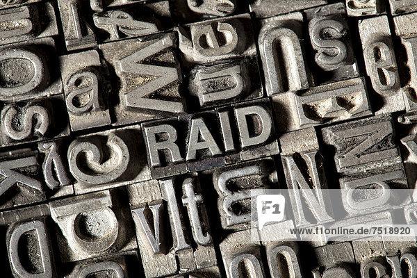 'Alte Bleilettern bilden das englische Wort ''RAID'''