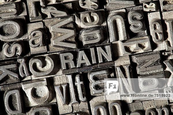 'Alte Bleilettern bilden das englische Wort ''RAIN'''