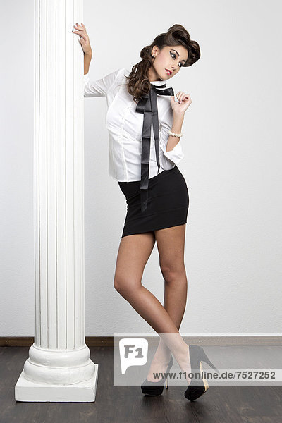 Junge Frau mit weißer Bluse  kurzem schwarzem Rock und hohen Schuhen posiert an Säule