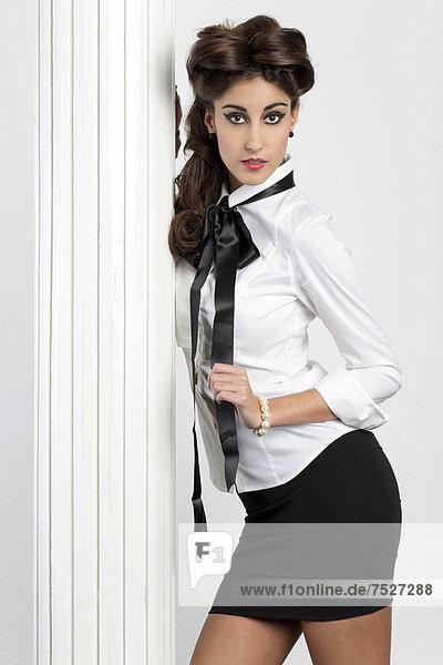 Junge Frau mit weißer Bluse und kurzem schwarzem Rock posiert an Säule