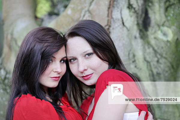 Two sisters in front of an old tree  portrait