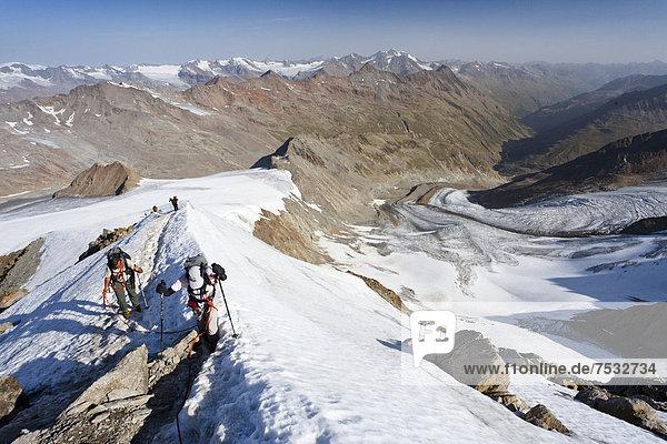 Wanderer auf dem Gipfelgrat beim Aufstieg zum Similaun auf dem Niederjochferner im Schnalstal  hinten der Marzell-Kamm  Südtirol  Italien  Europa