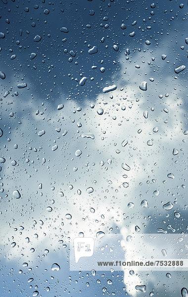 Regentropfen auf einer Scheibe  hinten Gewitterwolken