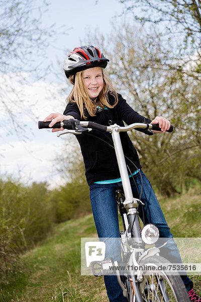 Mädchen mit Fahrradhelm und Fahrrad