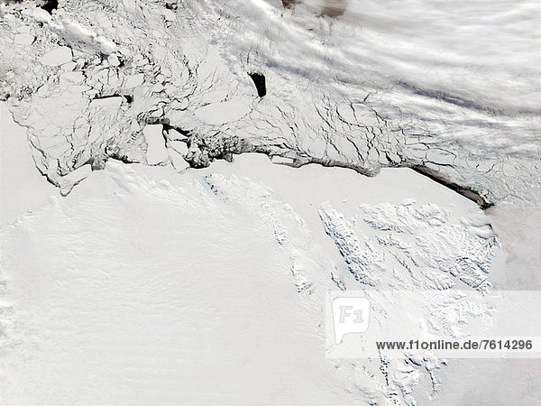 Sea ice begins to melt and break away from Oates Coast in the upper_half of This true_color image acquired from data collected on October 13  2001. As springtime progresses  and temperatures rise above freezing  the coastline of Antarctica becomes a visible reality. Also visible in the image  just to the right of center  under heavy snow are the Usurp Mountains running north and south. To the right of the Usurps is another mountain range  the Bowers Mountains. The Bowers Mountains are the more defined  angular formations closer to the coastline. In between the two ranges is a sleek  gray sheet  which marks the Rennick Glacier.