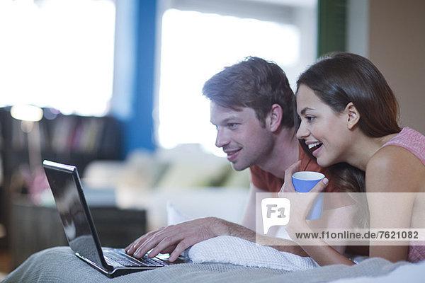 Paar mit Laptop zusammen auf dem Bett