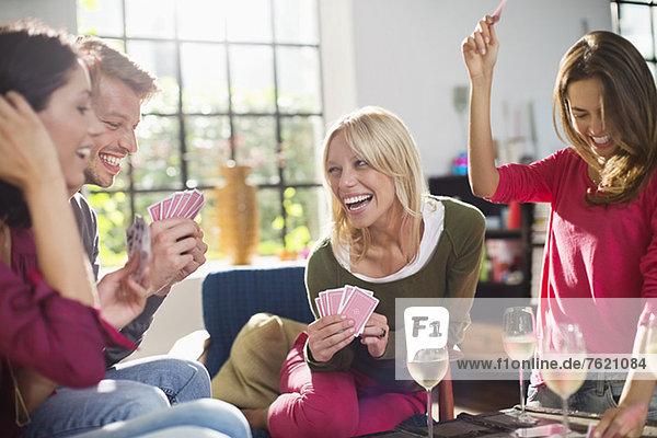 Freunde spielen Kartenspiel im Wohnzimmer