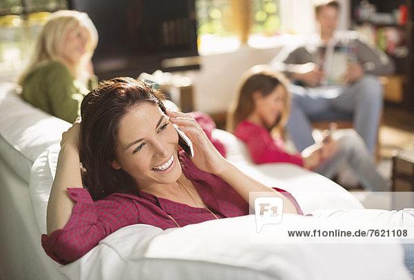 Frau spricht am Telefon auf dem Sofa