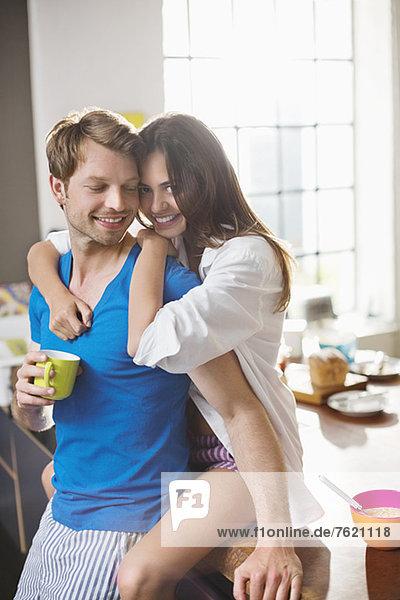 Lächelndes Paar umarmt sich in der Küche