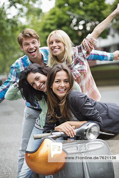 Freunde lächeln auf dem Roller im Freien