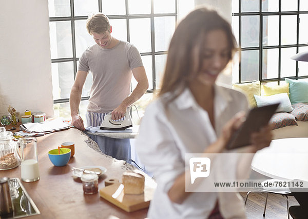 Frau mit digitalem Tablett als Freundesbügeleisen in der Küche