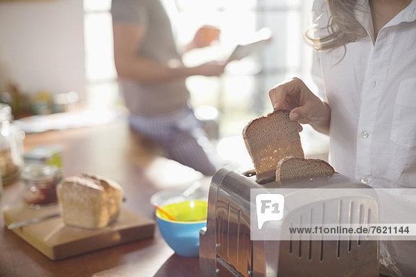 Frau legt Brot in den Toaster