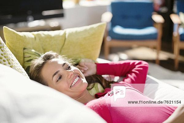 Lächelnde Frau entspannt auf dem Sofa