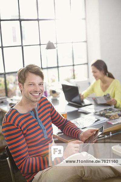 Lächelnder Mann mit digitalem Tablett