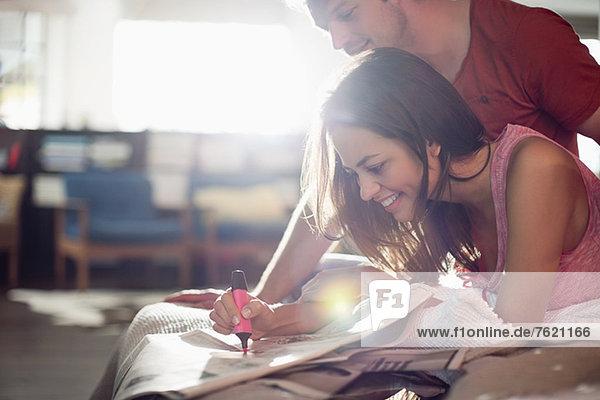 Paar liest Zeitung zusammen auf dem Bett