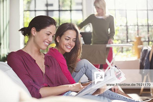 Frauen beim gemeinsamen Lesen auf dem Sofa