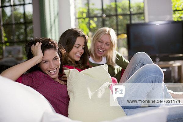 Frauen lachen gemeinsam auf dem Sofa