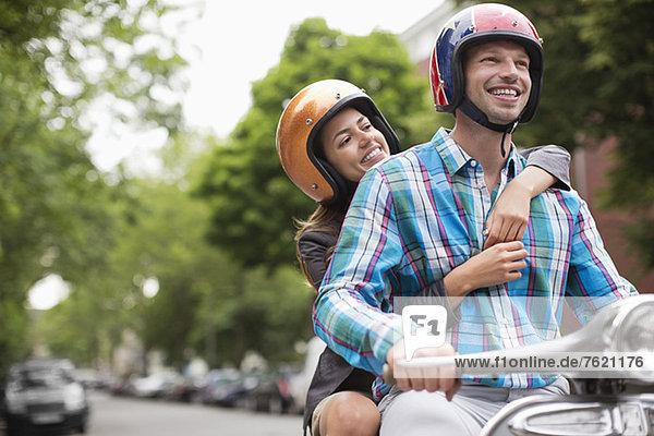 Paare fahren Roller zusammen im Freien