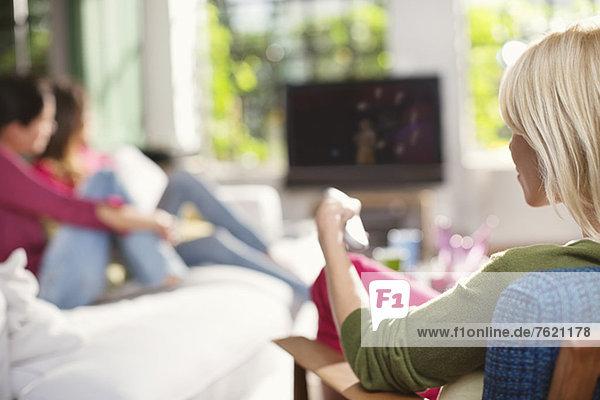 Frau wechselt den Kanal im Fernsehen