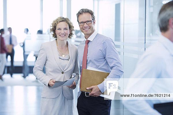 Geschäftsleute lächeln im Büroflur
