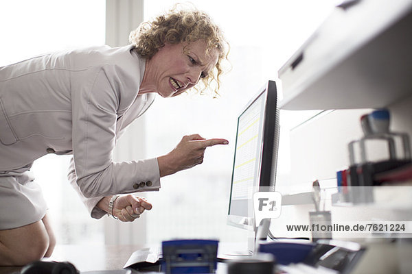 Geschäftsfrau schreit Computer im Büro an