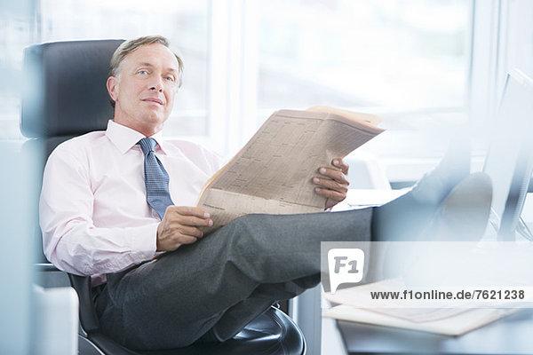Geschäftsmann liest Zeitung im Büro